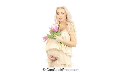 Pregnant woman in a pink dress holding a bouquet of tulips...
