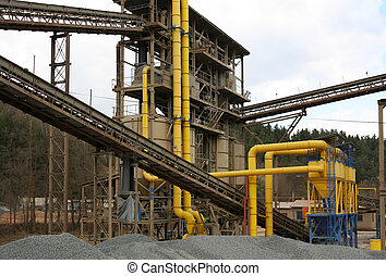 Stone quarry with silos, conveyor belts and piles of stones.