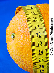 An orange and a measuring tape isolated on blue concepts of healthy diet