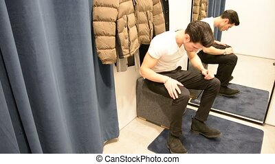 Young Man Trying on Shoes in Clothing Store - Rear View of a...