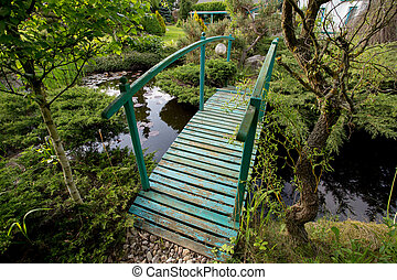 small green footbridge over a pond - small green footbridge...