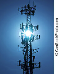 Cell tower#2 - Cell tower back lit by sun on a clear blue...