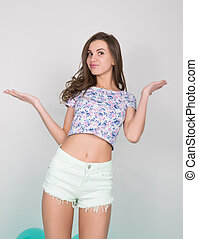 beautiful curly girl in multi-colored top, white shorts and...