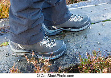 Hiking boots on studded wooden footbridge - Close up photo...