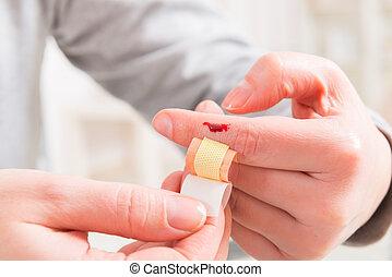 Applying adhesive bandage on finger - Applying adhesive...