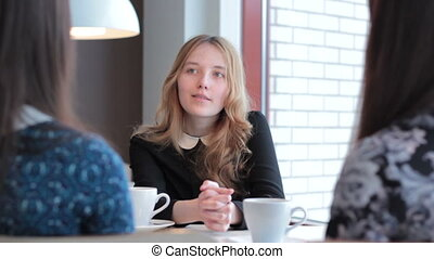 Girl tells the story her girlfriends in cafe.