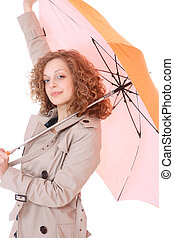 Woman holding an umbrella wearing trenchcoat standing on...
