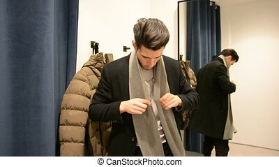 Young Man Trying on Clothes in Clothing Store - Rear View of...