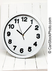 White kitchen clock with black numbers on a white background.