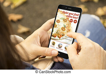 woman ordering food with phone in the park