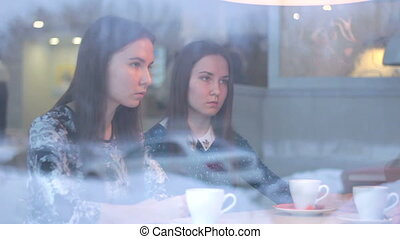 Twins talking with a friend while looking at each other in cafe