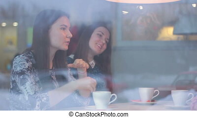 Twinsl young girls talk in a cafe in winter