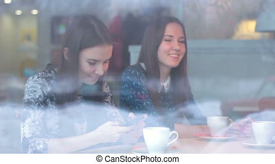 Beautiful girl showing a smartphone girlfriend in cafe