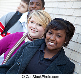 Multi-racial college students against a brick wall -...