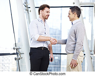 corporate people shaking hands - two caucasian business...
