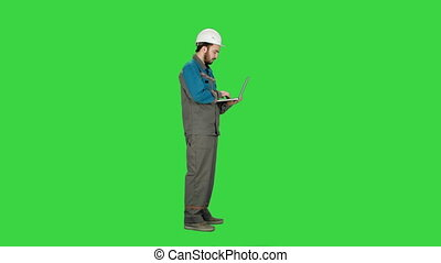 Attractive engineer using laptop on a Green Screen, Chroma Key.