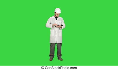 Technician building site using tablet to check progress on a Green Screen, Chroma Key.