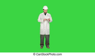 Healthcare professional, doctor, nurse, dentist, researcher, physician assistant, reading text sms, message on cell phone on a Green Screen, Chroma Key.