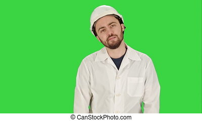 Frustrated workman in helmet over on a Green Screen, Chroma...