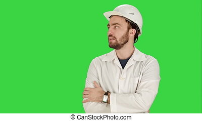 Construction worker looking at his watch. Builder waiting for a meeting on a Green Screen, Chroma Key.
