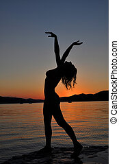 Silhouette of a sexy woman in sunset on the beach