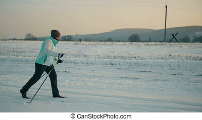Teenager learning how to ski in the blue sky ant mountains background