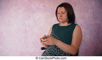 woman sitting collect the Rubik's Cube - woman sitting...