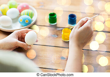 close up of woman coloring easter eggs - easter, holidays,...