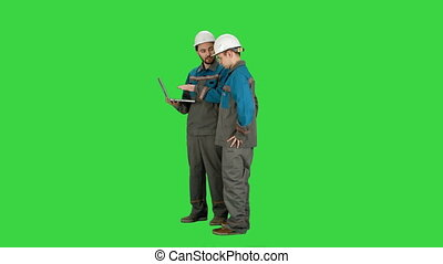 Supervisors using laptop at construction site on a Green Screen, Chroma Key.
