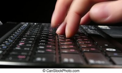 Hand of an office worker typing on black keyboard, close up,...