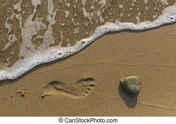 Heart rock - Heart shaped rock washed by the sea on a sandy...