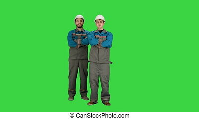 Industry, building, construction and people concept - happy male builders on a Green Screen, Chroma Key.