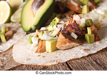Carnitas Pork with onion and avocado on tortilla close-up....