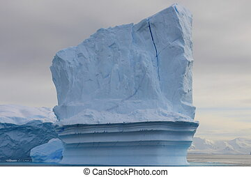 Towering iceberg in Antarctica with clouds in background