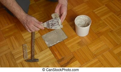 Handyman Fixing Damaged Parquet - Handyman gluing pieces of...