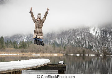 Woman in mid-air jumping near lake - Single excited woman...