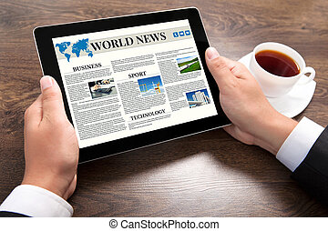 businessman holding tablet computer with world news site on screen