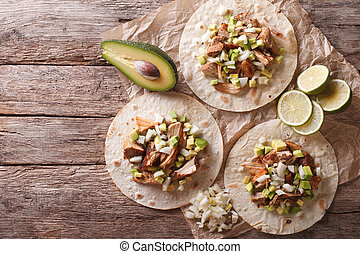 Mexican food: tortilla with carnitas, onions and avocado....