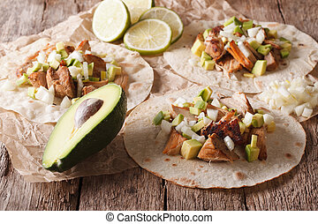 Mexican tacos with carnitas, onions and avocado close-up....