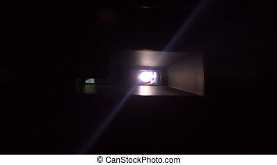 projector lens with beam of light at cinema