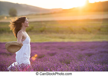 Running through a field of lavender - Beautiful young...