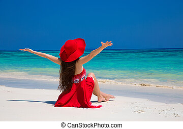 Beautiful woman in hat enjoying and relaxing on beach with...