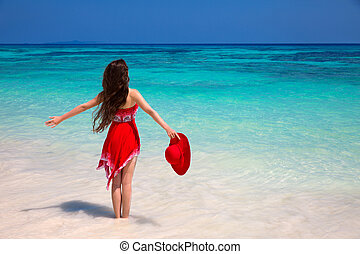 Happy woman enjoying on exotic beach in summer by tropical...