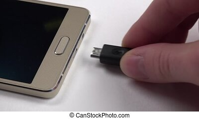 Hand using charging of mobile phone on white, close up -...