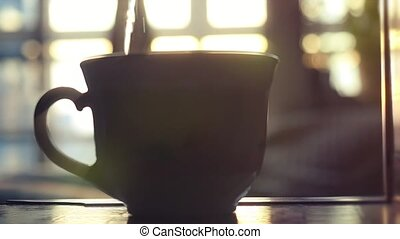 kettle pouring boiling water into a cup during breakfast in...