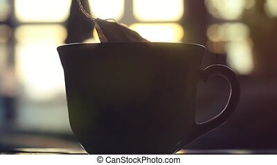 teabag puts in Cup of teain slowmotion on sunshine....