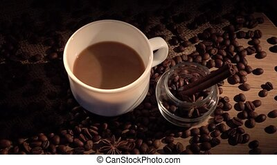 Coffee beans, cup, with star anise and cinnamon on sackcloth, cam moves to the right, shadow