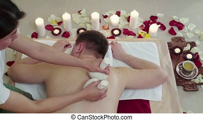 Man in Spa Resort Massage Bags with Aromatic Herbs - Man in...