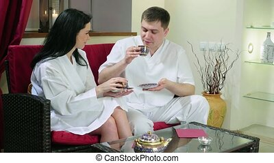Young Woman and Man Sitting on Sofa Drinking Tea