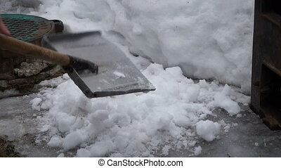 man cleans snow shovel in  yard